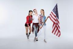 Femmes se tenant avec le drapeau américain d'isolement sur le blanc Photos stock