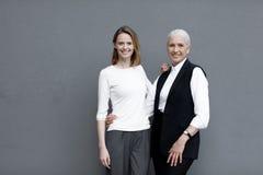 Femmes se tenant ensemble et souriant d'isolement sur les jeunes gris, et supérieurs Photos stock