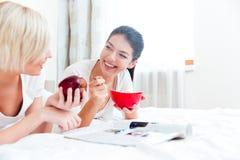 Femmes se trouvant sur le lit avec la nourriture et la magazine Photos stock