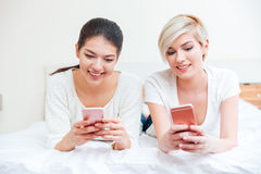 Femmes se trouvant sur le lit et à l'aide des smartphones Photos libres de droits