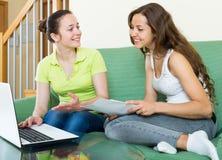 Femmes semblant les documents financiers avec l'ordinateur portable Photo libre de droits