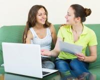 Femmes semblant les documents financiers avec l'ordinateur portable Image stock