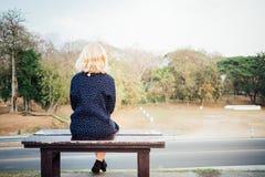 Femmes seul s'asseyant sur un amour de attente de banc Image libre de droits