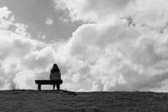 Femmes seul s'asseyant sur un amour de attente de banc Photographie stock libre de droits