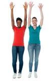 Femmes soulevant leurs bras dans l'excitation Images stock