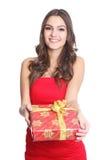 Femmes souriant avec un cadeau dans sa main Photographie stock libre de droits