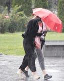 Femmes sous le parapluie pendant la douche soudaine de ressort Photo libre de droits