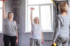 Femmes sportives agréables s'exerçant dans un centre de fitness Images stock
