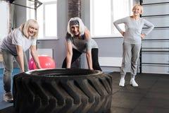 Femmes sportives avec plaisir soulevant un pneu énorme Image libre de droits