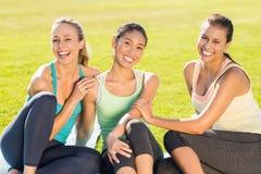 Femmes sportives de sourire s'asseyant sur la terre Images libres de droits