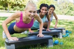 Femmes sportives faisant l'aérobic d'étape Photos stock