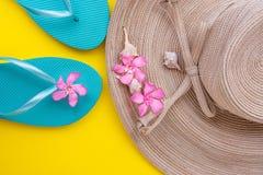 Femmes Straw Hat avec les coquilles bleues de mer de pantoufles de fleurs tropicales de rose d'arc sur le déplacement jaune de bo photographie stock libre de droits