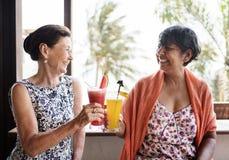 Femmes supérieures appréciant des boissons pendant l'été Image libre de droits