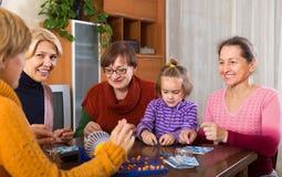 Femmes supérieures avec l'enfant au bureau avec le bingo-test Photos libres de droits