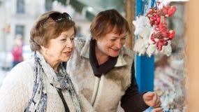 Femmes supérieures choisissant des décorations au compteur du marché de Noël Photos stock