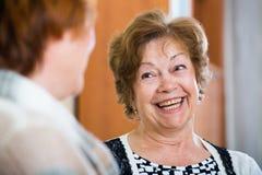 Femmes supérieures heureuses ayant la causerie à la maison Image stock