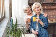 Femmes supérieures heureuses détendant avec la tasse de la boisson chaude Photos libres de droits