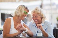 Femmes supérieures riant en café de rue Photo stock