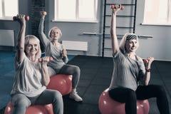 Femmes supérieures s'exerçant avec des haltères sur des boules d'équilibre Photographie stock libre de droits