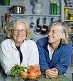 Femmes supérieures se penchant au comptoir de cuisine Photos stock