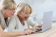 Femmes supérieures souriant et à l'aide de l'ordinateur portable Photographie stock