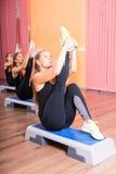 Femmes sur des plates-formes de forme physique étirant leurs jambes Photo libre de droits