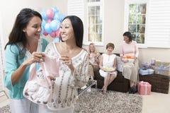 Femmes tenant des vêtements de bébé à la fête de naissance Images stock
