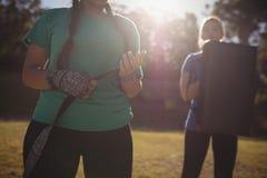 Femmes tenant l'équipement de boxe pendant le parcours du combattant Image stock
