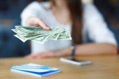 Femmes tenant le dollar en main et l'asseyant contre le concept d'affaires Image stock