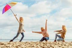 Femmes tenant le parapluie ayant l'amusement avec des amis image stock