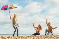Femmes tenant le parapluie ayant l'amusement avec des amis photographie stock libre de droits