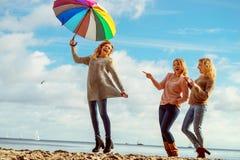 Femmes tenant le parapluie ayant l'amusement avec des amis image libre de droits