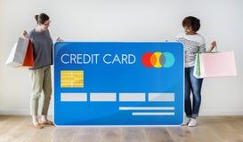 Femmes tenant une carte de crédit avec des paniers Images stock