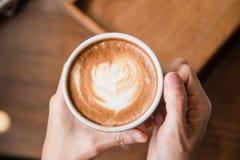 Femmes tenant une tasse de café chaude dans des mains dans le café Photographie stock