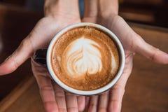 Femmes tenant une tasse de café chaude dans des mains dans le café Image stock