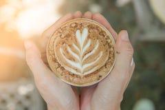 Femmes tenant une tasse de café chaude dans des mains dans le café Image libre de droits