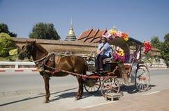 Femmes thaïlandaises de voyageurs posant avec le chariot hippomobile avant tou Photo libre de droits