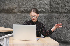 Femmes étonnées portant les lunettes, chemise noire dans le café regardant dans l'ordinateur portable Photographie stock