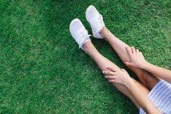Femmes touchant sur des jambes avec la toile blanche Photographie stock