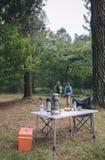 Femmes trimardant avec la table de camping dans le premier plan Images stock