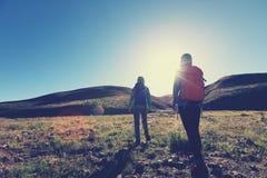 femmes trimardant en montagnes de lever de soleil Photos libres de droits
