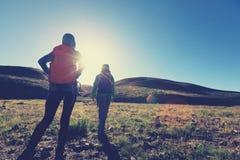 femmes trimardant en montagnes de lever de soleil Photographie stock libre de droits