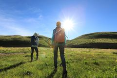 femmes trimardant en montagnes de lever de soleil Images stock
