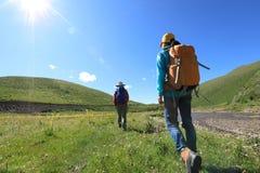 Femmes trimardant en montagnes de rive Photographie stock libre de droits
