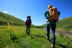 Femmes trimardant en montagnes de rive Image stock