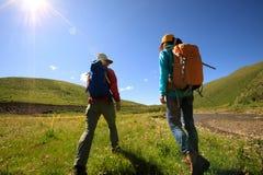 Femmes trimardant en montagnes de rive Images libres de droits