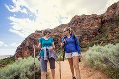 Femmes trimardant ensemble dans un beau canyon rouge de roche photographie stock libre de droits