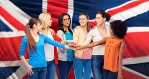 Femmes unies de nternational au-dessus de drapeau britannique Photographie stock libre de droits