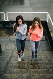 Femmes urbaines de forme physique courant et montant des escaliers Photo libre de droits