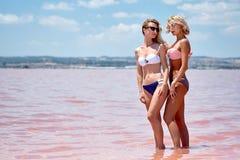 Femmes utilisant des maillots de bain posant au lac de sel photo stock